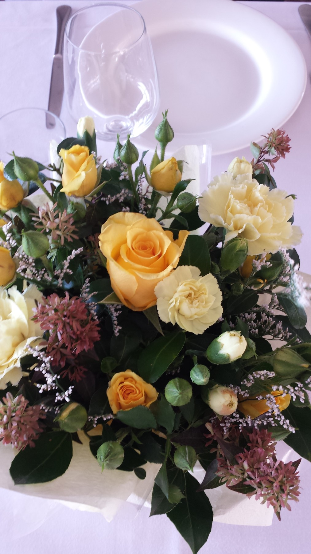 table flowers yellow roses, spray carnations and foliages
