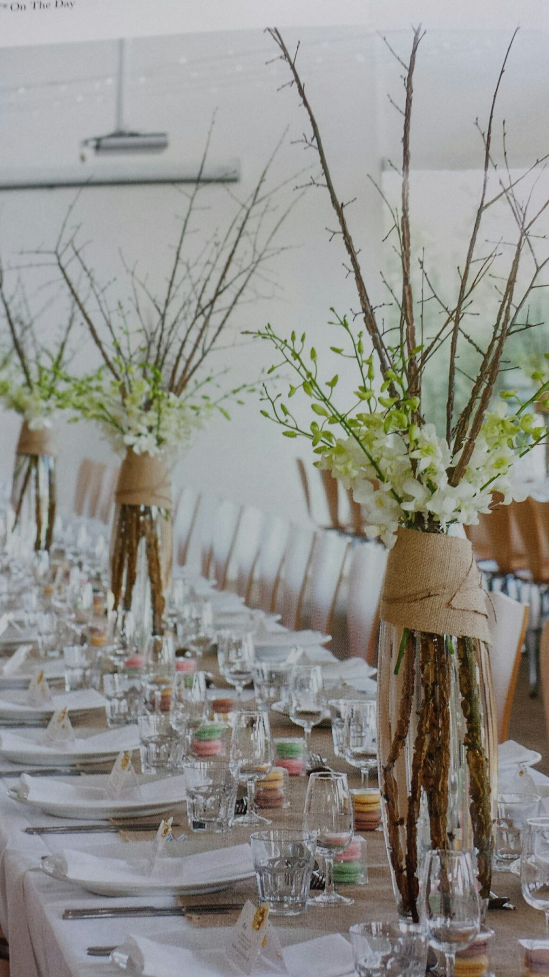 Tall glass vases with sticks and orchids wrapped in hessian
