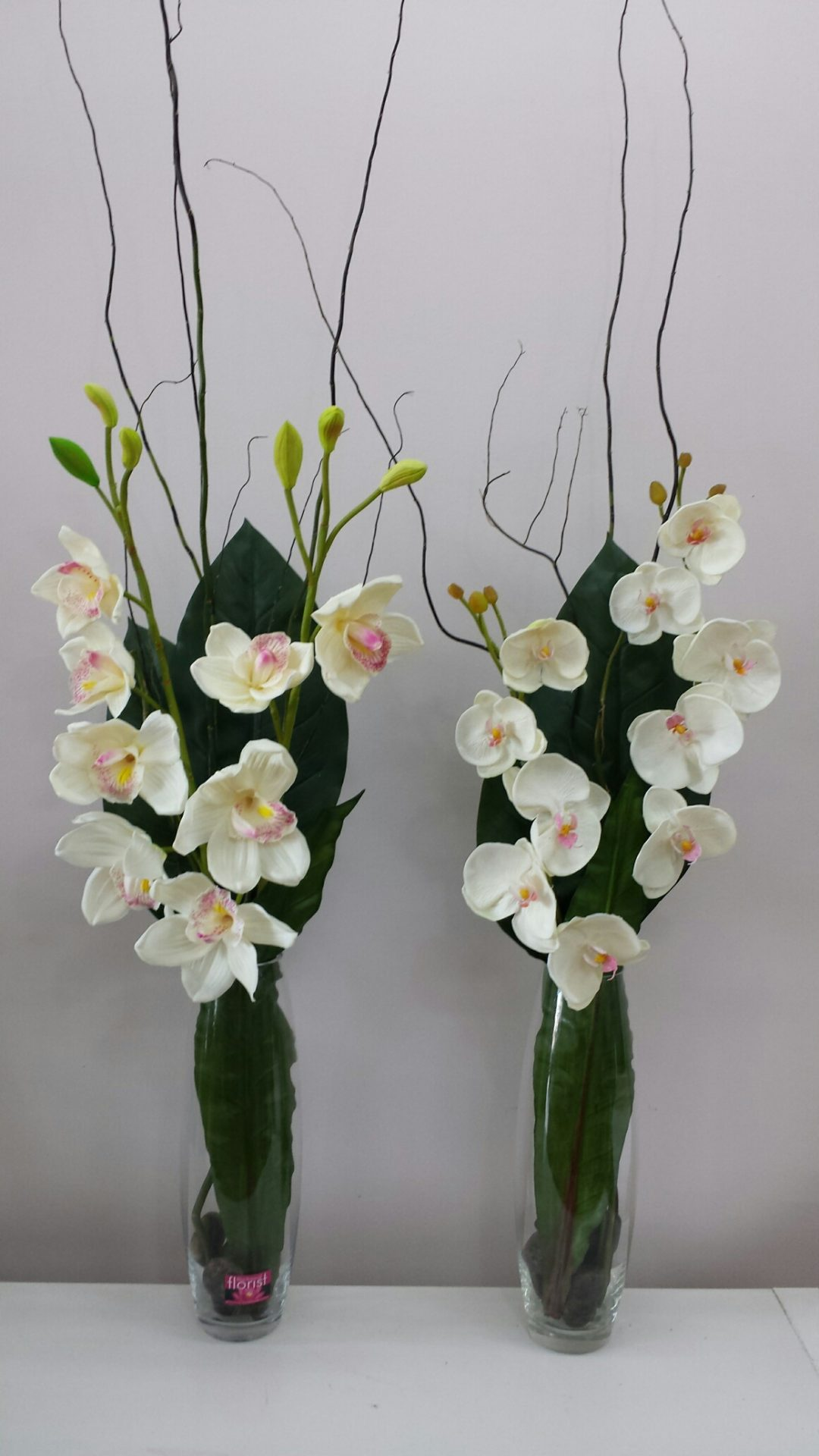 Tall glass vases with Orchids and willow sticks