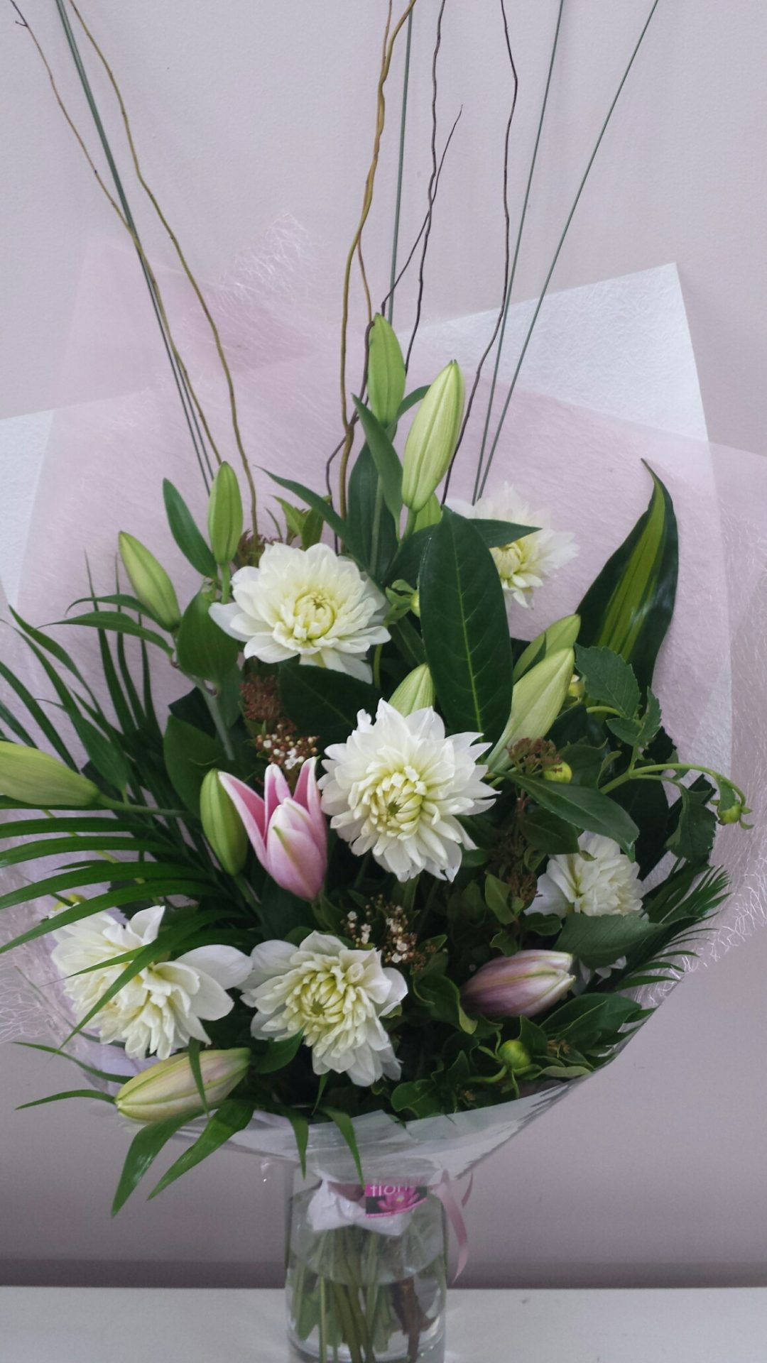 aduation bouquet lilies and dahlias with tropical foliages