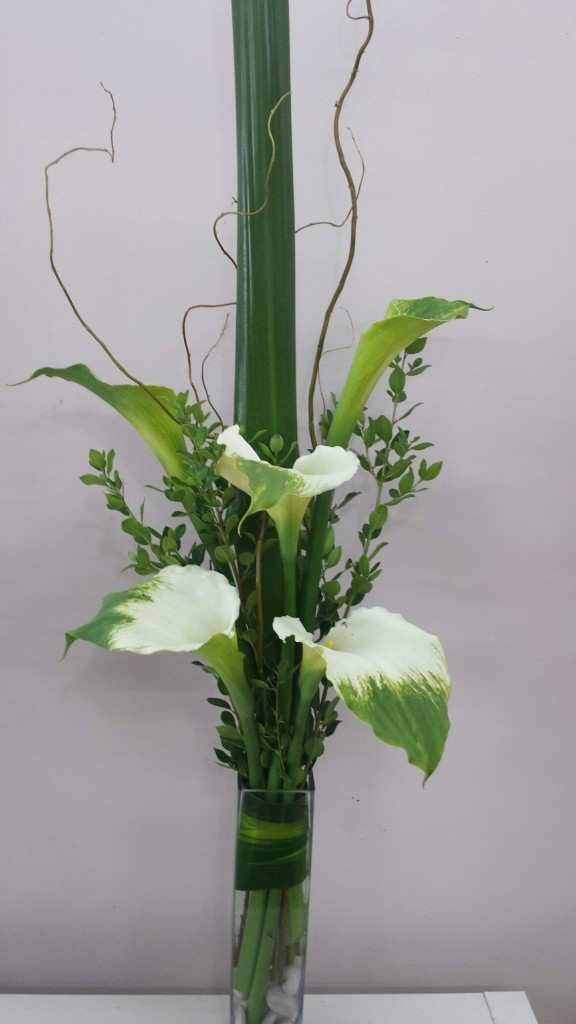 Green goddess lilies in a glass vase with willow