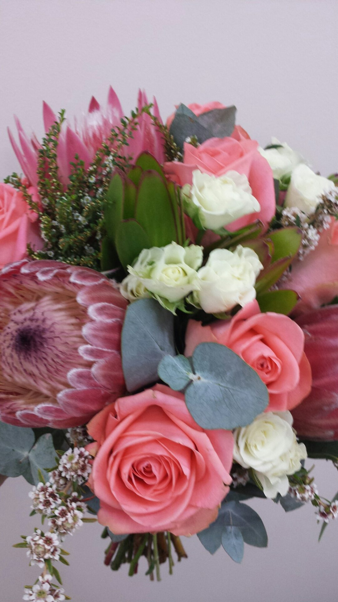 gathered bouquet of natives, roses and blue gum foliage