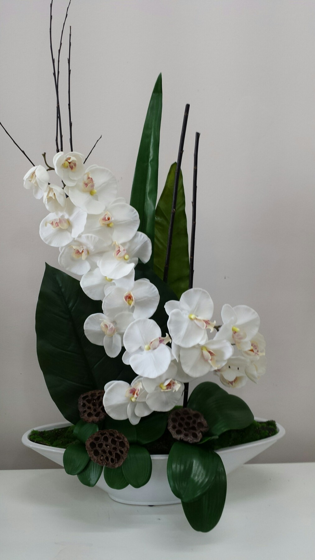 Orchid stems with lotus pods in a ceramic boat shaped pot