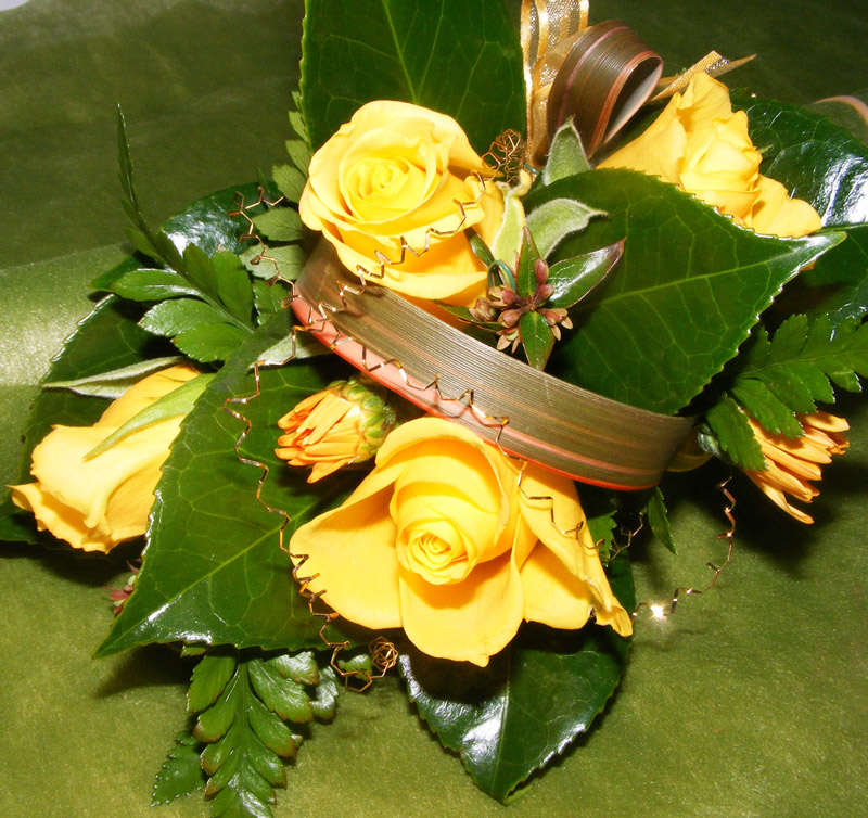 Wrist style corsage with gold roses and loops of flax