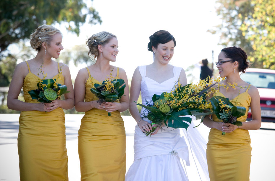 yellow orchids, succulents and tropical foliage arm sheaf style bouquet