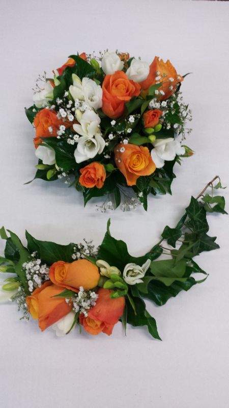 Cake top and base featuring orange roses, fressia and green orchids