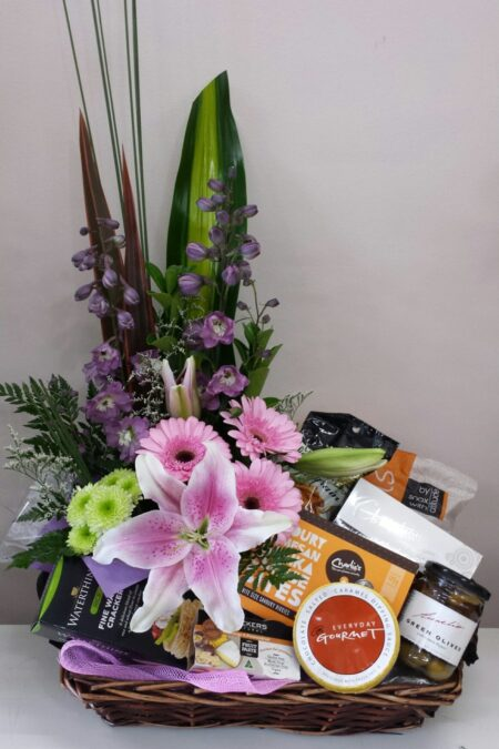 Selection of gourmet products with flower arrangement on one side