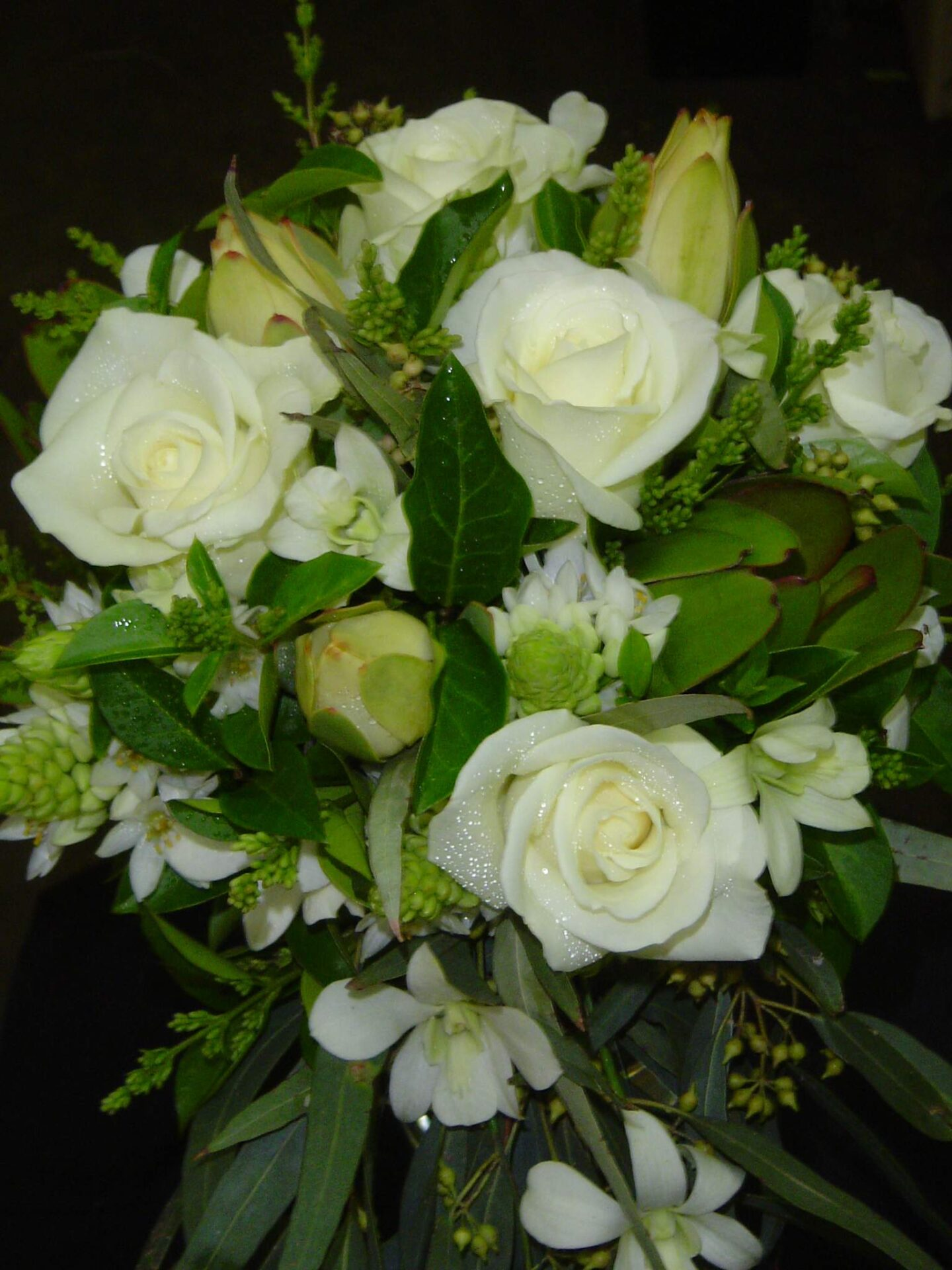 White roses, orchids, alstromerium and gum leaves trailing style bouquet