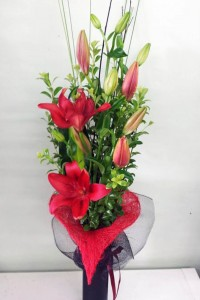 Red lilies and foliage in a glass vase with love heart.