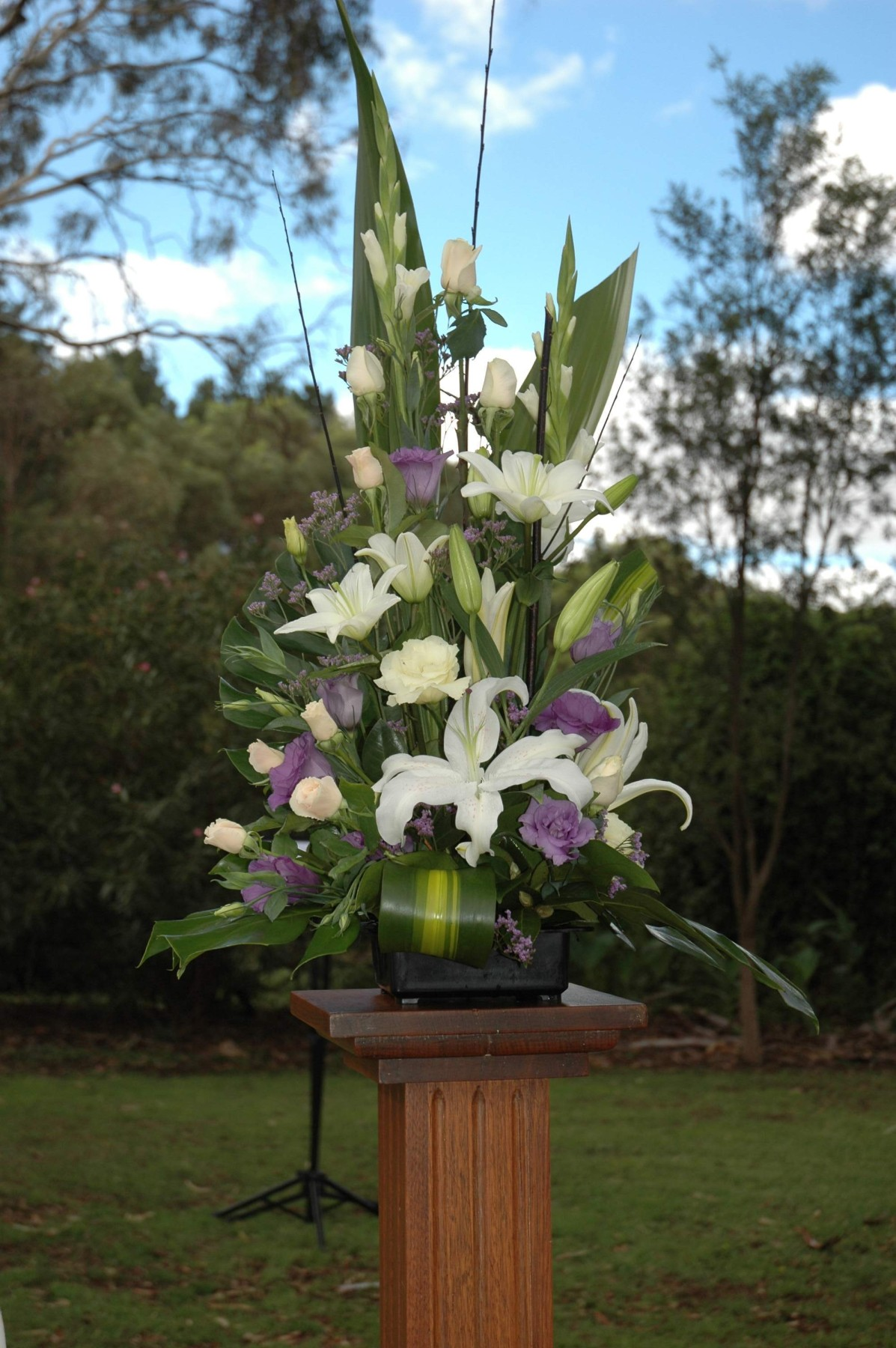 pedestal arrangement white lilies, lisianthus and roses