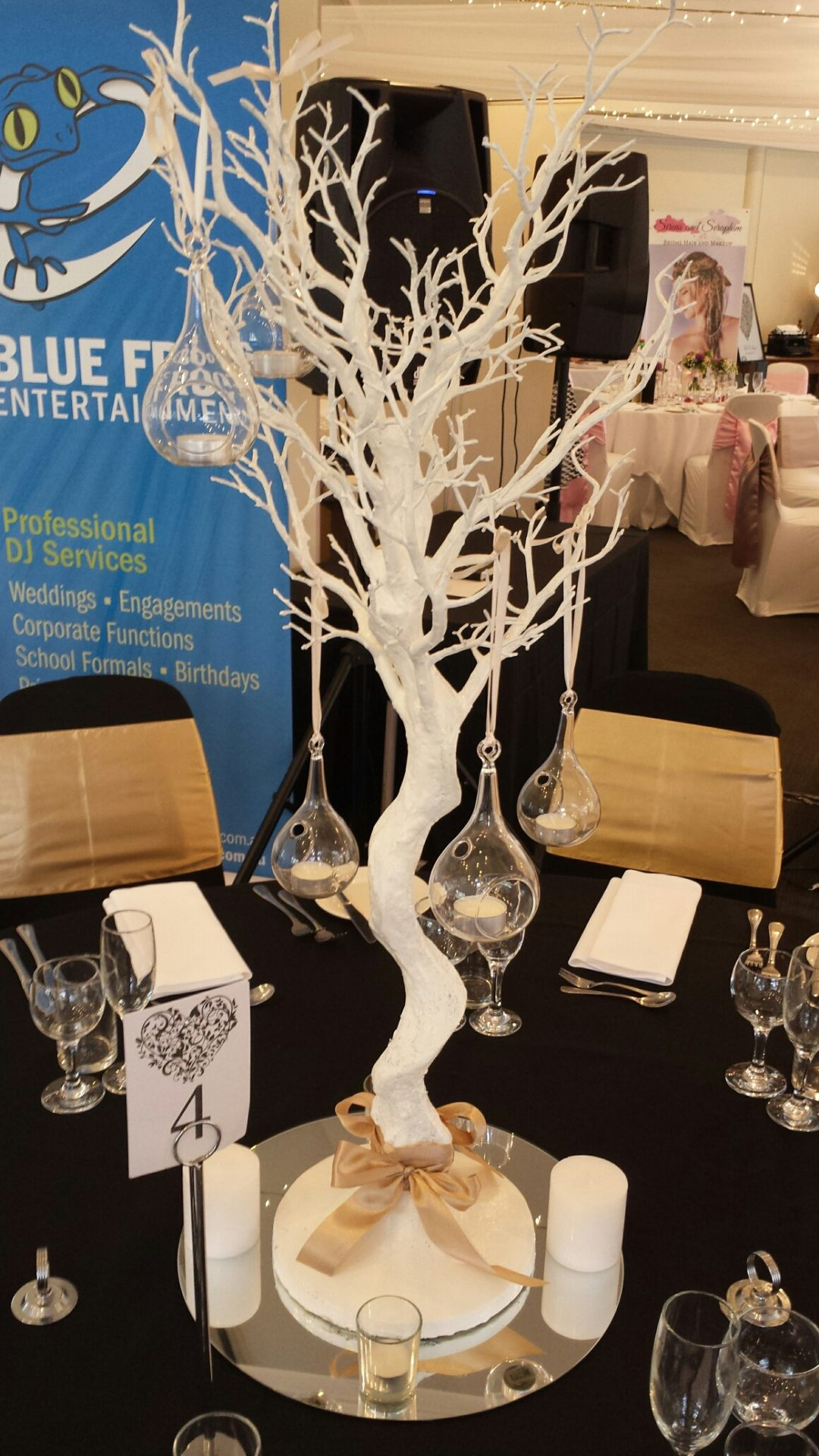 White tree with hanging glass vases and candles