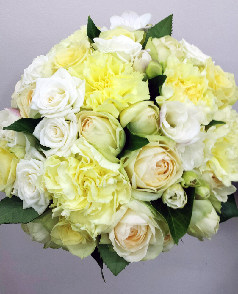 Lemon carnations, white spray roses and ivory rose bridal bouquet