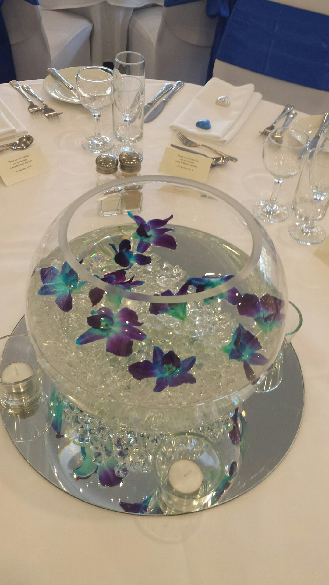 Large glass fish bowl with floating Singapore orchid blooms
