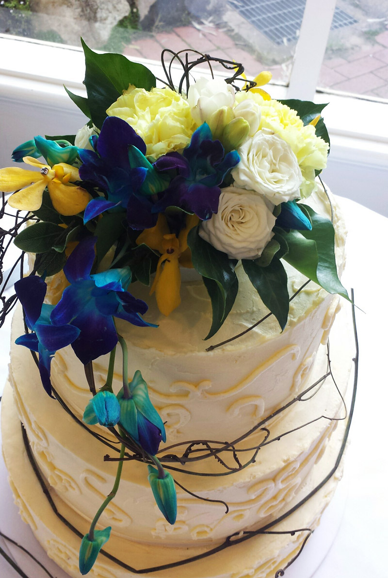 Trailing cake top with white roses and blue and yellow orchids