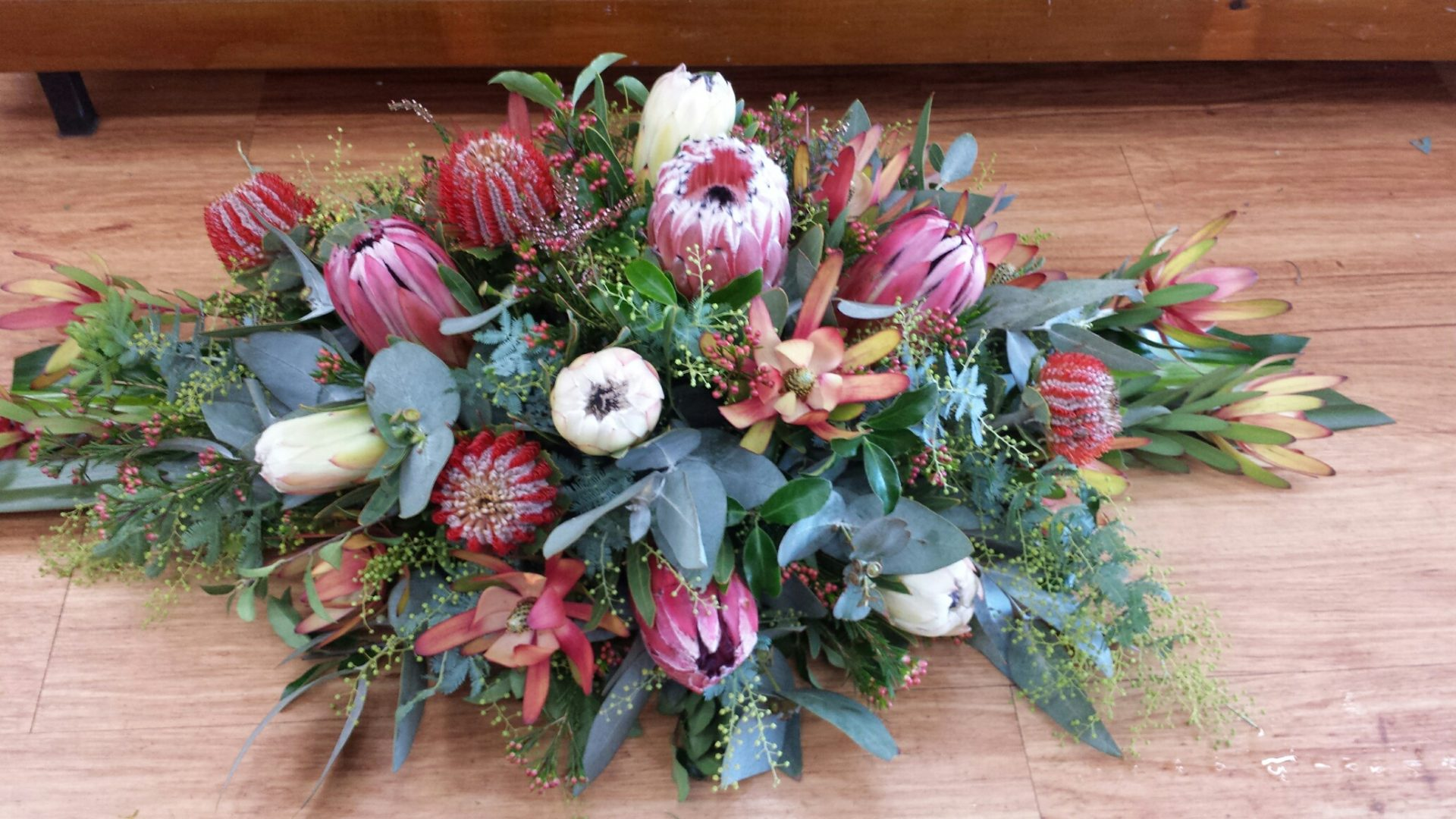 Casket spray featuring mix of native and wild flowers, blue gum and wax