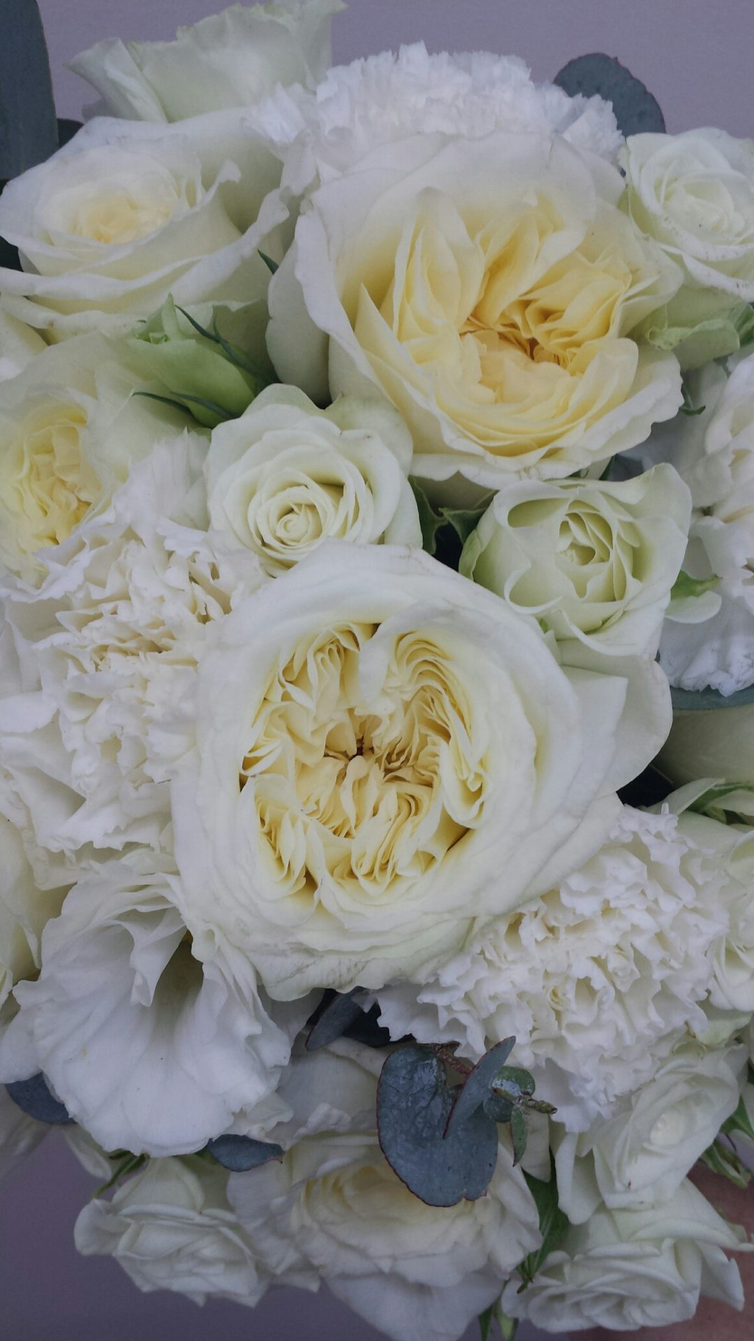 All white David Austin and garden roses, spray roses, Lisianthus and carnation bouquet
