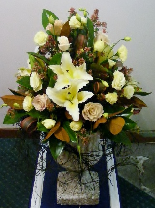 Church arrangement round - magnolia, lilies and roses in an urn.