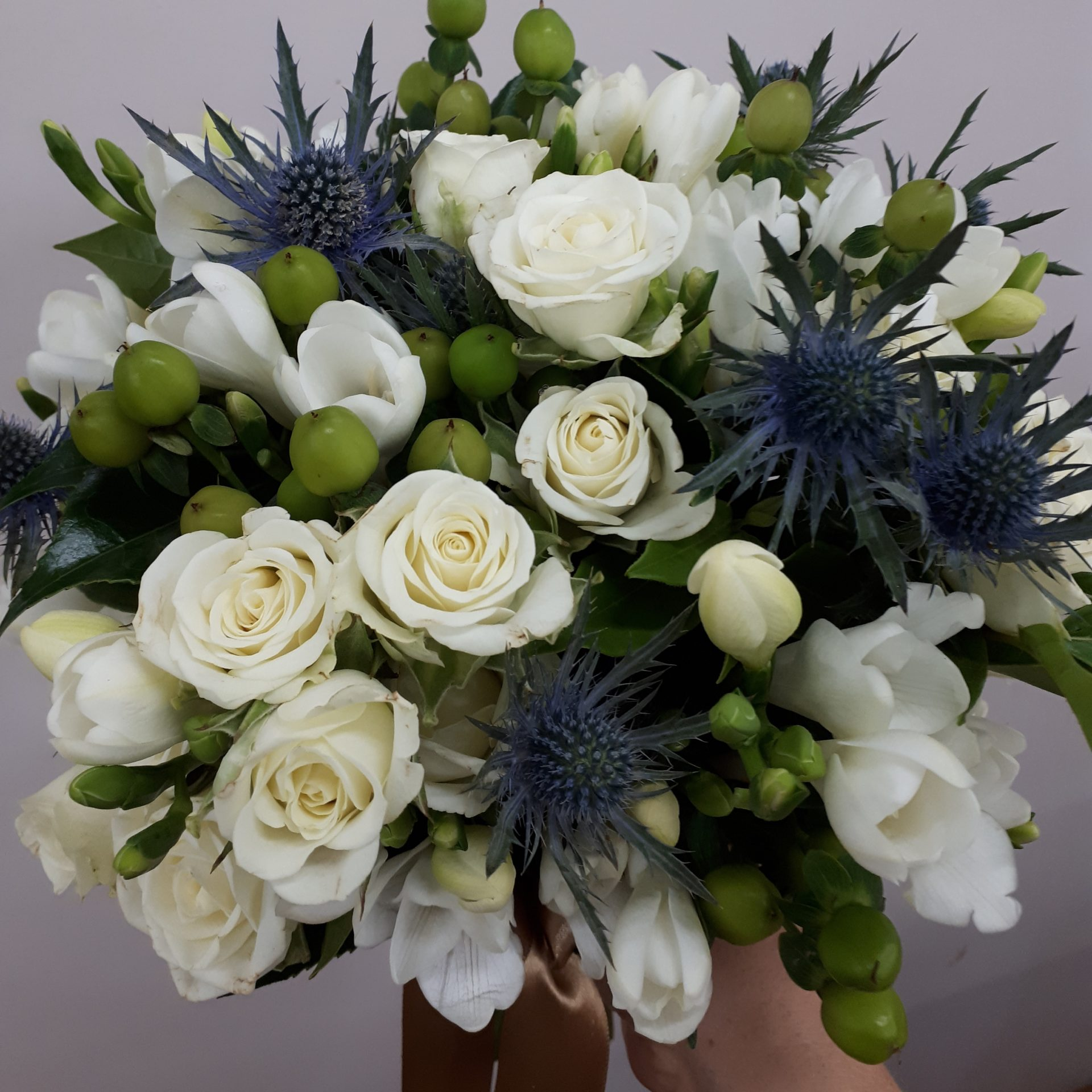 Compact posy sea holly, freesia ,spray roses and hypericum berries