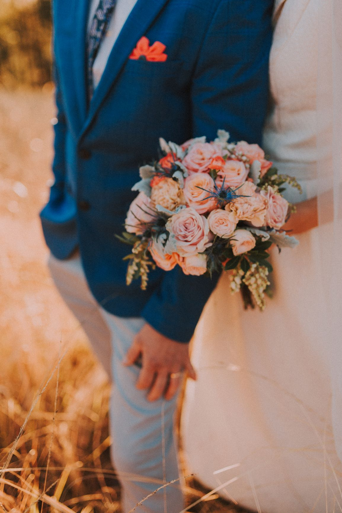 Soft pink roses, apricot spray roses, sea holly and cascading andromeda