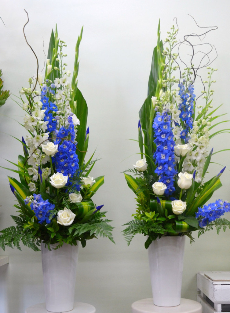 Pedestal arranegment with white and blue flowers and tropical leaves