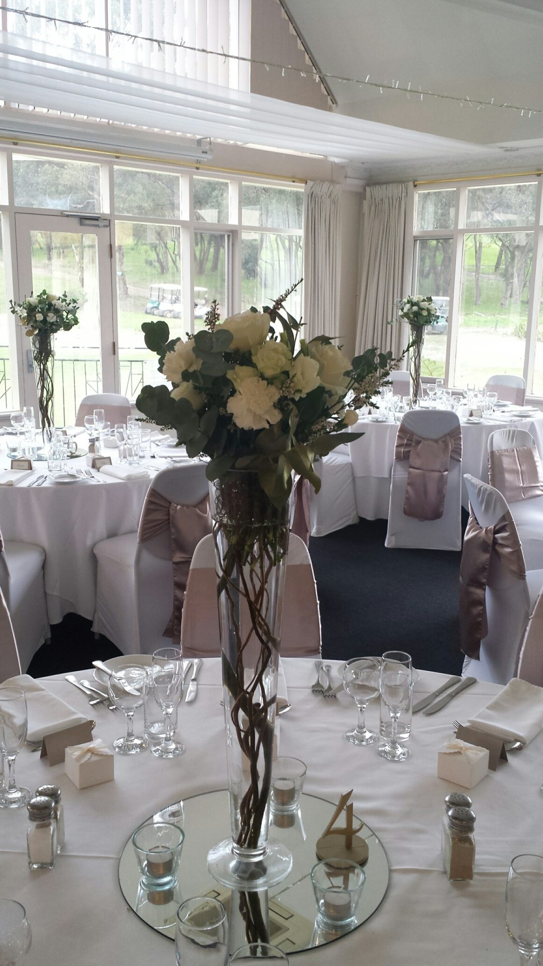 tall glass vases with willow inside and white posy ontop
