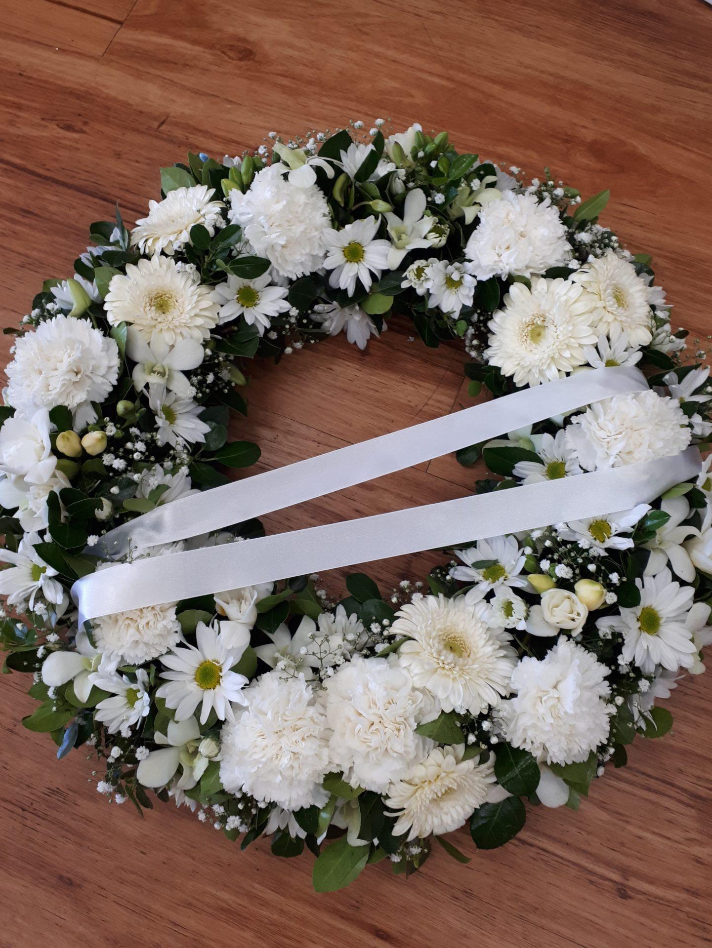 white mixed flower wreath with ribbon